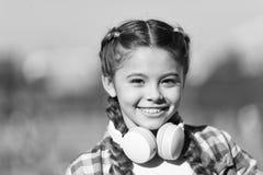 Ребенок девушки слушает музыка outdoors с современными наушниками Репертуар счета музыки подгоняет вашу музыку Открывать новый стоковая фотография rf