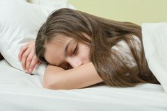 Ребенок девушки с длинными коричневыми волосами спать на подушке в кровати Стоковое Изображение
