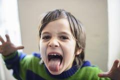 Ребенок делает гримасы стоковое изображение