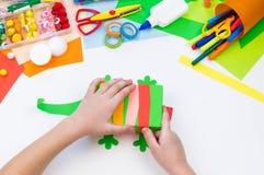 Ребенок делает хамелеона коробки мотыги Материал для творческих способностей на белой предпосылке стоковая фотография
