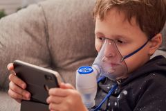 Ребенок делает nebulizer вдыхания дома на стороне носить nebulizer маски вдыхая пар распылил лекарство в легких  стоковые фотографии rf