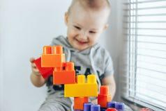 Ребенок делая кирпичи игрушки Башня игрушки ребёнок счастливый фокус на игрушках Младенец несосредоточенный Стоковые Фото