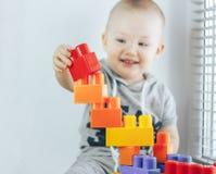 Ребенок делая кирпичи игрушки Башня игрушки ребёнок счастливый фокус на игрушках Младенец несосредоточенный Стоковое фото RF