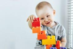 Ребенок делая кирпичи игрушки Башня игрушки ребёнок счастливый фокус на игрушках Младенец несосредоточенный Стоковые Изображения