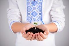 Ребенок держа молодой завод с почвой в руках как зачатие дня земли Стоковое фото RF