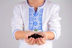 Ребенок держа молодой завод с почвой в руках как зачатие дня земли Стоковые Фотографии RF