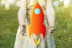Ребенок держа чертеж ракеты как startup концепция outdoors на a Стоковые Изображения
