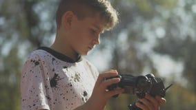 Ребенок держит автомобили дистанционное управление и автомобиль игрушки Мальчик с автомобилем игрушки outdoors видеоматериал