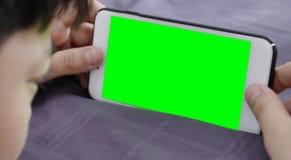 Ребенок держит телефон в его руке с зеленым экраном стоковые фотографии rf