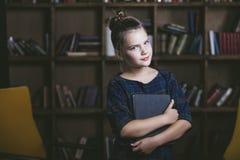Ребенок девушки в библиотеке с книгами в строгой моде enga Стоковое Изображение RF