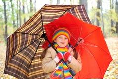 Ребенок девушки в лесе осени с зонтиком, красивым ландшафтом в сезоне падения с желтыми листьями Стоковое фото RF