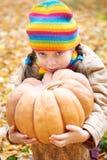 Ребенок девушки в лесе осени с тыквой и яблоками, красивым ландшафтом в сезоне падения с желтыми листьями Стоковое Изображение RF