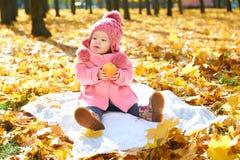 Ребенок девушки в парке осени с корзиной яблок, красивым ландшафтом в сезоне падения с желтыми листьями Стоковая Фотография