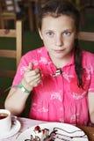 Ребенок девушки есть торт в кафе Стоковые Изображения RF
