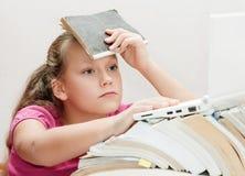 Ребенок девушки при книга смотря компьтер-книжку Стоковое Изображение RF
