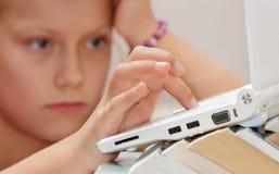 Ребенок девушки при книга смотря компьтер-книжку Стоковая Фотография RF