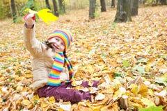 Ребенок девушки сидит в лесе осени, красивом ландшафте в сезоне падения с желтыми листьями Стоковое Изображение RF