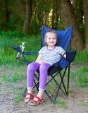 Ребенок девушки сидит на стуле в лесе на пикнике семьи Стоковое Изображение RF