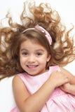 Ребенок девушки с длинной ложью волос на белизне и открытых оружиях, одетых в пинке Стоковое Изображение RF