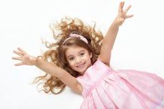 Ребенок девушки с длинной ложью волос на белизне и открытых оружиях, одетых в пинке Стоковые Фото