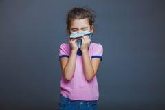 Ребенок девушки чихает в носовой платок на сером цвете Стоковые Изображения
