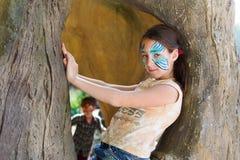 Ребенок девушки outdoors в дереве с картиной стороны бабочки Стоковое Изображение