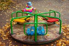 Ребенок едет carousel в спортивной площадке ` s детей в осени девушка немногая играя Стоковые Изображения
