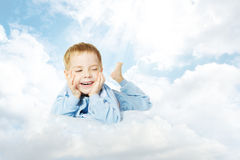 Ребенок лежа вниз на подушке облака над небом Стоковое фото RF