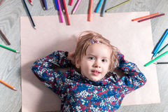 Ребенок лежа на бумаге пола около crayons Картина маленькой девочки, чертеж Взгляд сверху lego руки творческих способностей принц Стоковые Фото