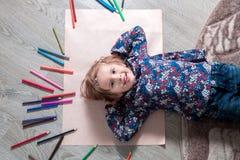 Ребенок лежа на поле бумажном смотрящ камеру около crayons Картина маленькой девочки, чертеж Взгляд сверху lego руки творческих с Стоковое Изображение RF