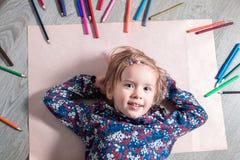 Ребенок лежа на поле бумажном смотрящ камеру около crayons Картина маленькой девочки, чертеж Взгляд сверху lego руки творческих с Стоковые Фото