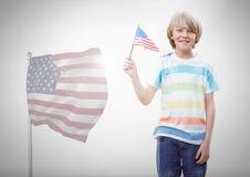 Ребенок держа американский флаг перед белой предпосылкой и американский флаг Стоковые Изображения RF