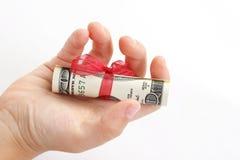 Ребенок держа в подарке руки долларовых банкнот американца 100 денег с красной лентой на белой предпосылке Стоковые Фото