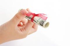 Ребенок держа в подарке руки долларовых банкнот американца 100 денег с красной лентой на белой предпосылке Стоковые Фотографии RF