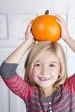 Ребенок держа малую тыкву на ее голове стоковая фотография