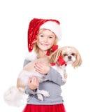Ребенок держа собаку нося шляпу Санты стоковые фото