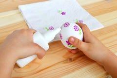 Ребенок держит пасхальное яйцо и клей decoupage в руках Ребенок клеит части цветка салфетки к яичку Decoupage пасхи Стоковое Фото
