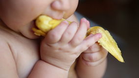 Ребенок есть банан с кожей сток-видео
