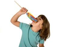 Ребенок есть большую конфету леденца на палочке изолированную на белой предпосылке в детях любит сладостную концепцию сахара и зу Стоковые Изображения