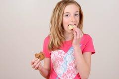 Ребенок есть высококалорийную вредную пищу стоковое изображение