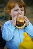 ребенок есть детенышей гамбургера Стоковое Изображение RF