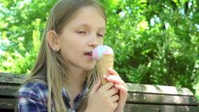 Ребенок есть мороженое на спортивной площадке, сидеть девушки ослабляя на Суде в парке 4K видеоматериал