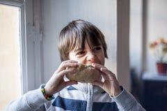 Ребенок ест большой домодельный хлеб Стоковые Фото