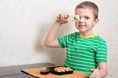 Ребенок ест крены суш дома стоковое фото