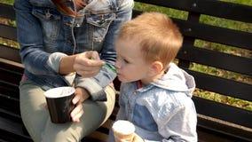 Ребенок ест мороженое сидя на стенде Молодая женщина и ребенок едят мороженое в парке на стенде Молодые акции видеоматериалы