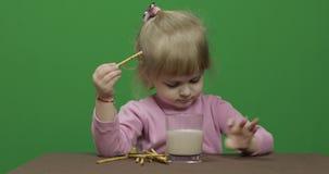 Ребенок ест печенья Маленькая девочка ест печенья сидя на таблице сток-видео