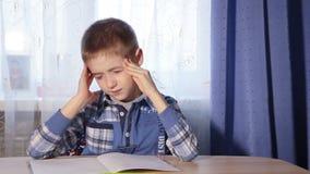 Ребенок делая головную боль домашней работы, мальчика усталости для того чтобы сделать видеоматериал
