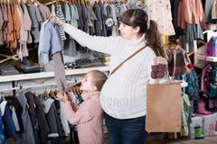Ребенок женщины и девушки выбирая одежды children's Стоковое Фото