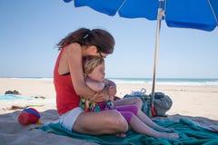 Ребенок женщины обнимая маленький на пляже смотря океан Стоковые Изображения