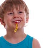 Ребенок жует камедеобразных медведей и смеется над Стоковая Фотография